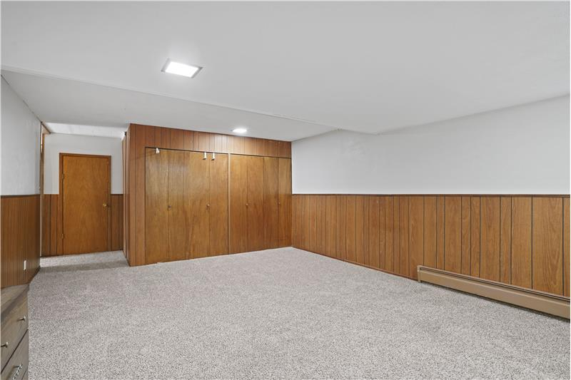 This large room with 3 closets and an above-grade window to the backyard could qualify as a 5th bedroom.