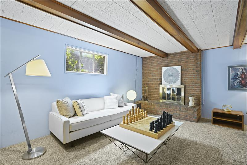 Basement family room has beamed ceiling, window well to the front yard and a wood-burning fireplace.