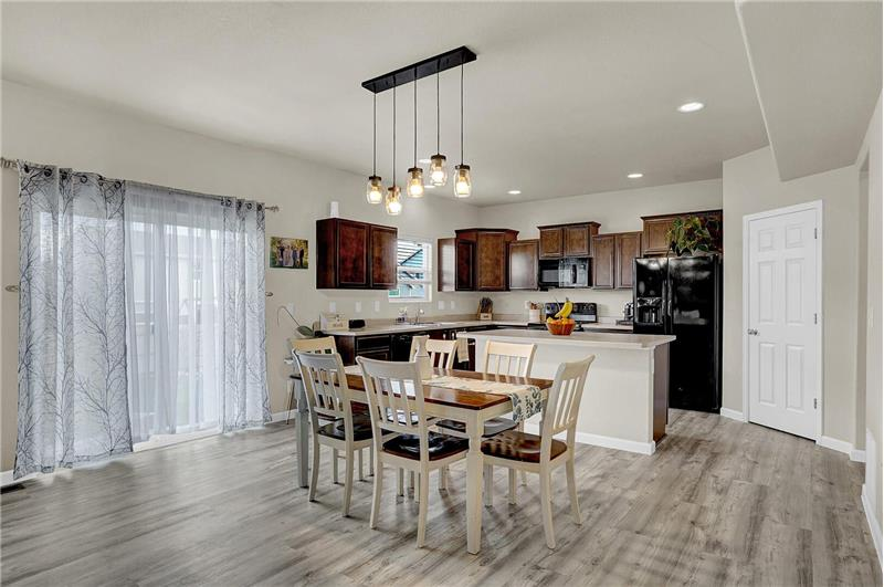 The walk-out Dining Area is off the Kitchen and features pendant lights