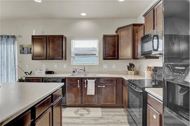 Appliances include a smooth top range oven, dishwasher, microwave, and side by side refrigerator