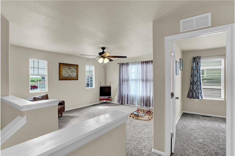 The upper level features a spacious loft with a lighted ceiling fan