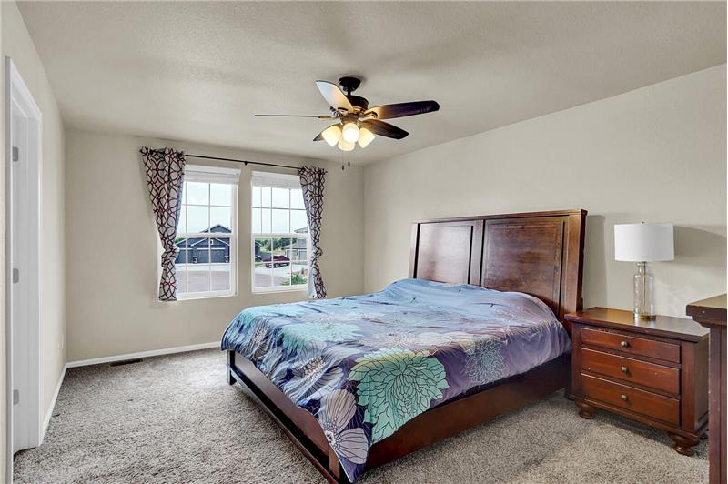 Upper-level Master Bedroom with neutral carpet, large window, and lighted ceiling