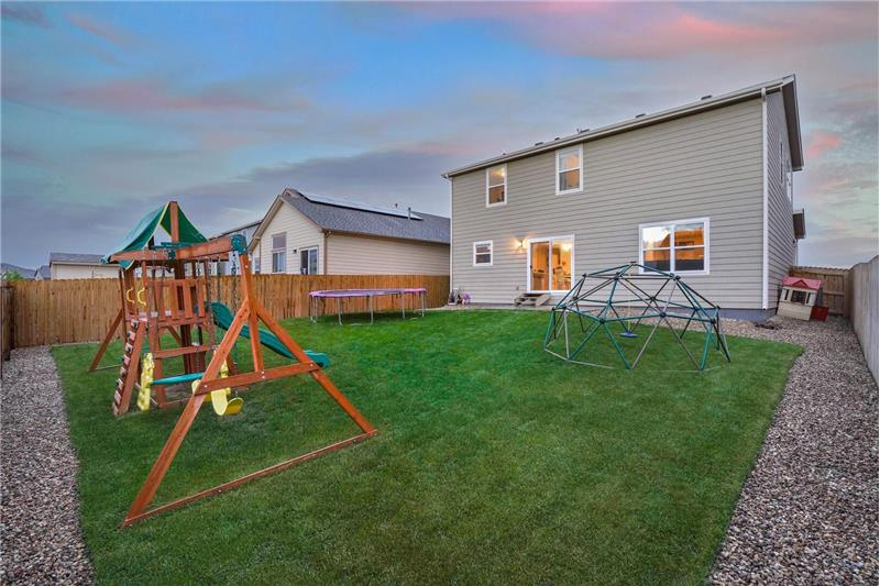 Nicely landscaped backyard with concrete patio for outdoor relaxation, and a playset with slide for the kids
