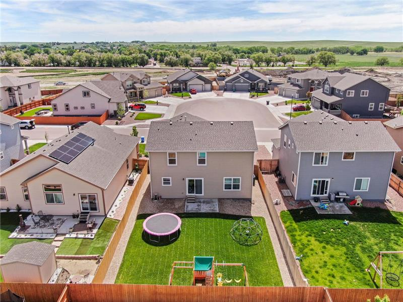Aerial view of backyard and neighborhood open space in the background