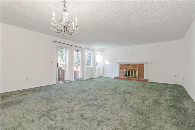 Dining Room/Living Room with wood-burning fireplace and door to fenced patio.