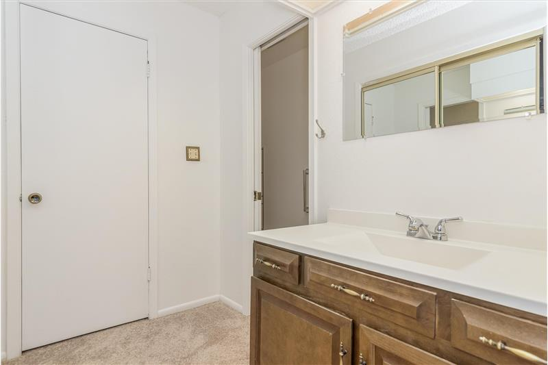 Master bathroom is divided into carpeted vanity area open to bedroom and separate room with toilet and shower and vinyl floor.
