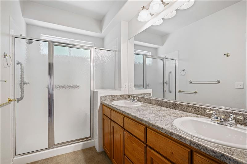 Master bathroom features shower with grab bars and bench