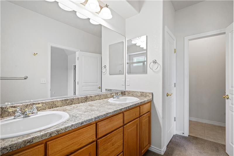 Reverse view of master bathroom showing linen closet and separate room for toilet