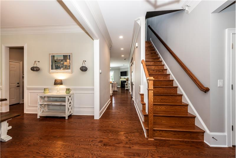 Foyer flanked by dining room and home office/study. Stairs to the second floor feature hardwood treads.