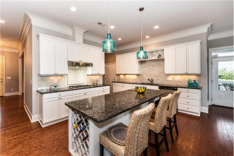 Cook's kitchen features custom cabinets, large center island with storage below, seating, and wine rack.