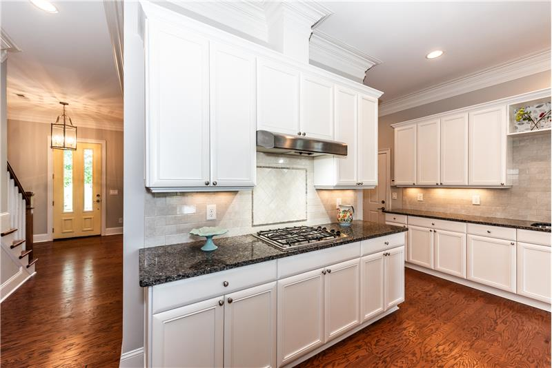 Gas burner cook-top, custom back-splash. Lots of counter and cabinet storage space + a pantry.