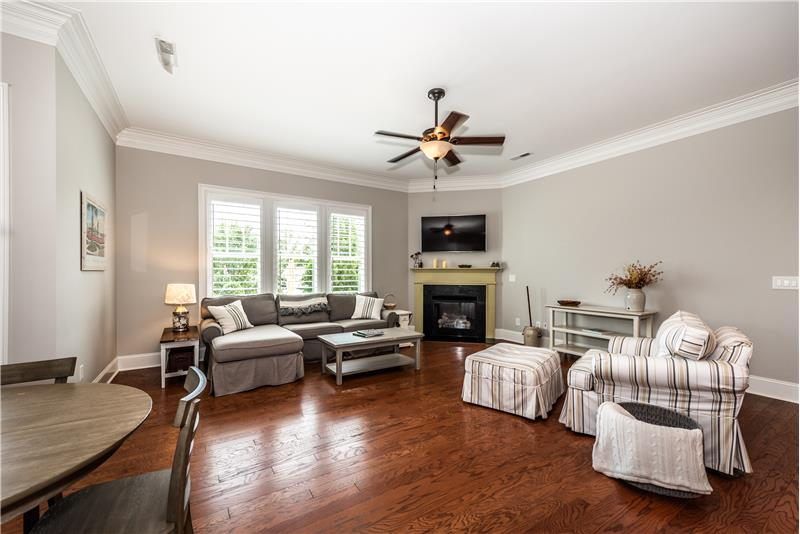 Large, open great room with gleaming hardwood floors, gas log fireplace with decorative mantel.