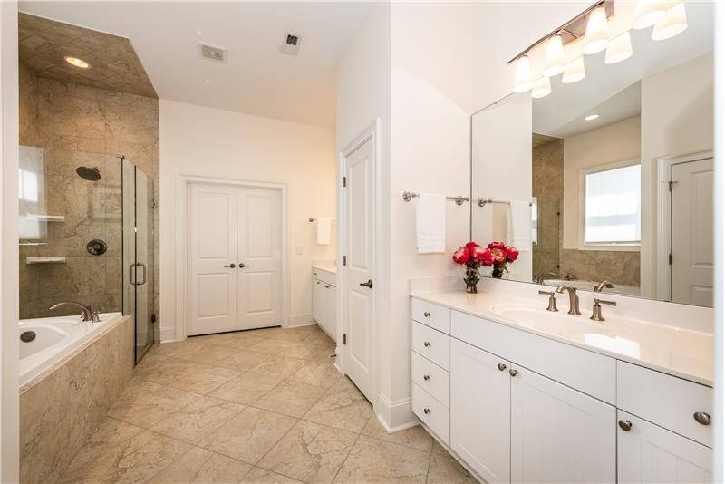 Spa-inspired master bathroom features dual vanities, tile floor and surround, walk-in closet, private water closet.
