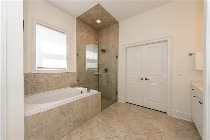Master bath features deep soaking tube, large frameless glass shower with tile surround. Window adds natural light.