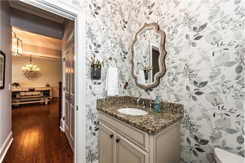 Pretty powder room with designer wallpaper, vanity with granite top, decorative mirror, window with plantation shutters.