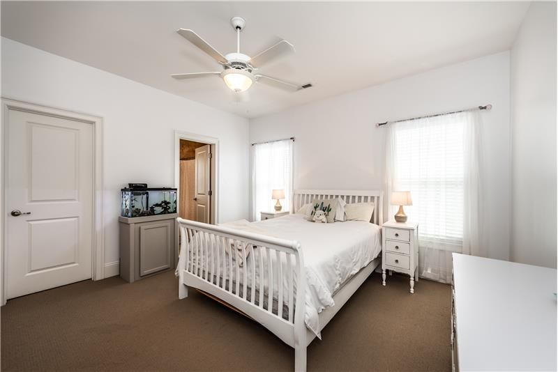 One of four secondary bedrooms on the upper floor of the home. This bedroom has an en-suite bathroom. Walk-in closet.