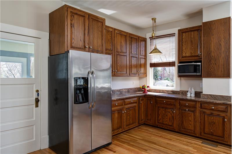 Kitchen features pull-down lighting, granite and stainless appliances