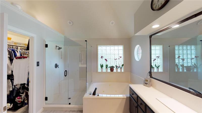 Frameless glass shower and his and hers closets!