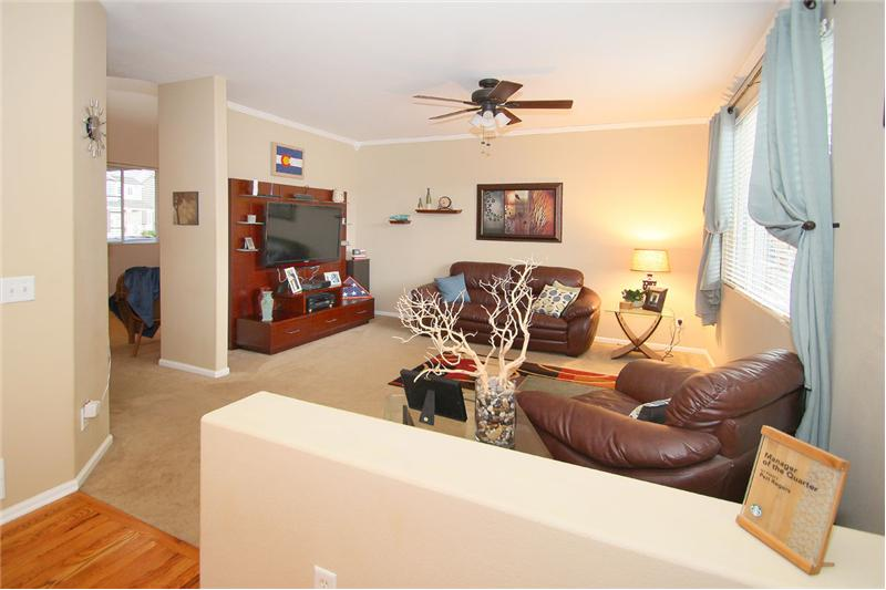 Spacious family room with ceiling fan and crown molding