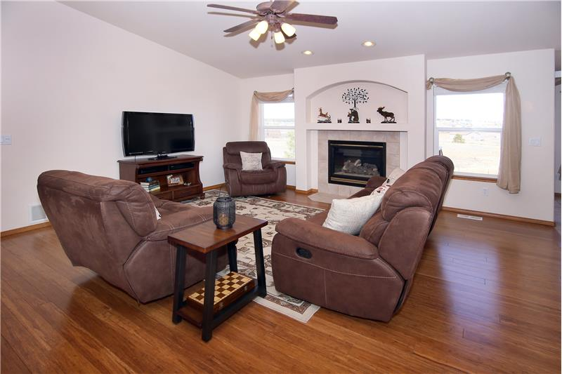 Great room with vaulted ceilings, ceiling fan, and bamboo flooring