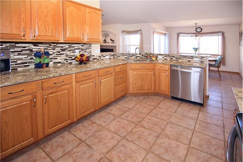 Granite counter tops, glass tile backsplash, and stainless steel appliances