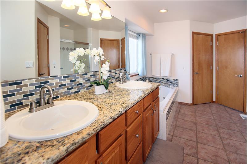 Granite counter tops, jetted tub, tile backsplash, and tile flooring