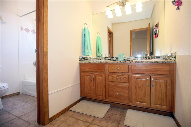 Full bathroom with double sinks, granite counters, and tile floors on main level