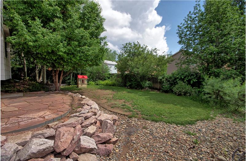 Fenced backyard with mature trees and a flagstone patio