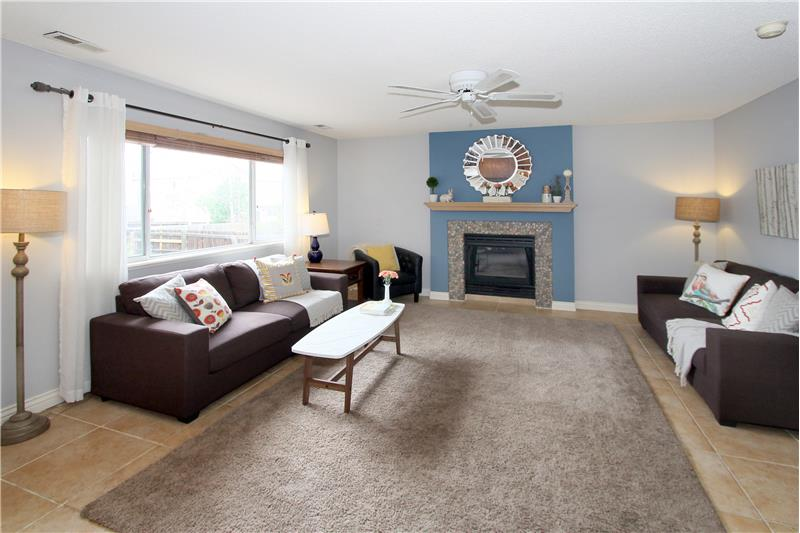 Family room with tile flooring, ceiling fan, and a gas fireplace