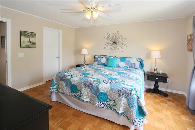 Walk-in closet, ceiling fan, and parquet flooring