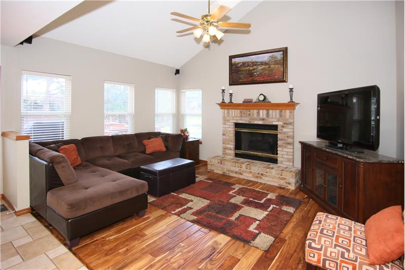 Family room with vaulted ceilings, teak hardwood flooring, a gas fireplace, and wired for surround sound!