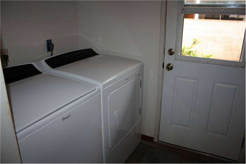 Laundry area (BRAND NEW Washer/Dryer!) and door to side yard and washing sink