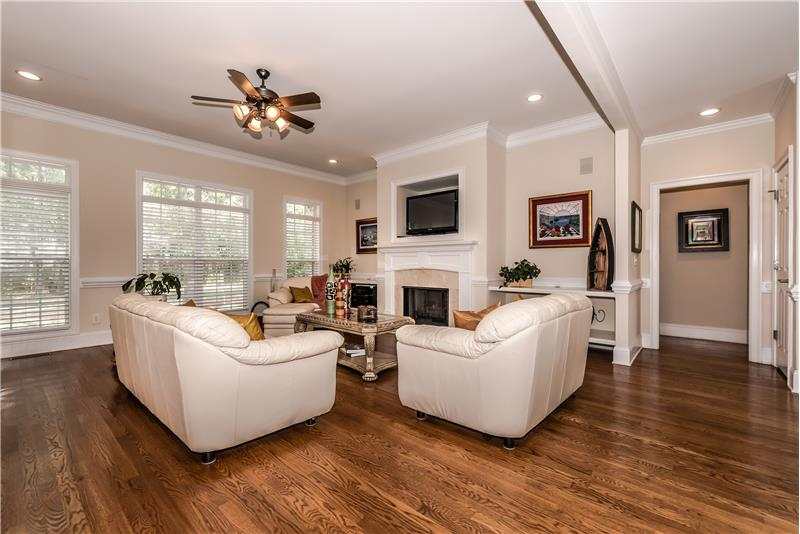 Large, open great room features hardwood floors, French-style windows with transoms, gas fireplace with decorative mantel.