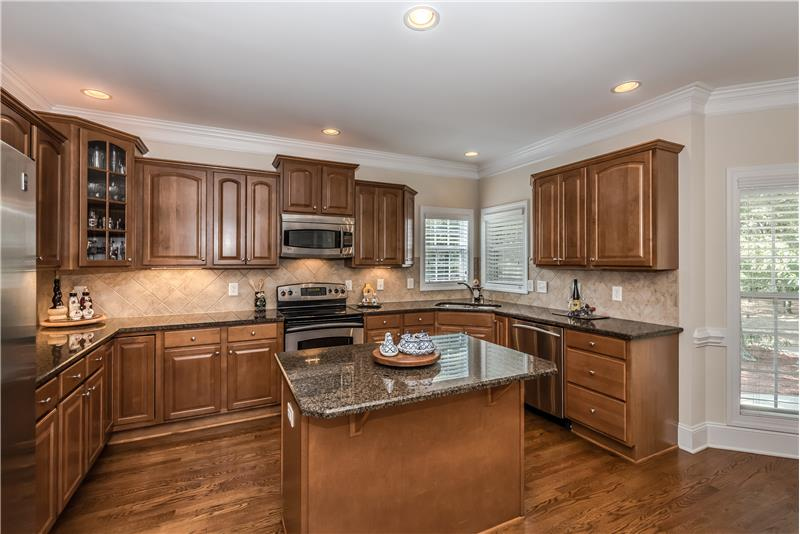 Kitchen features center island, stainless steel appliances, granite counters, title back splash, hardwood floors.