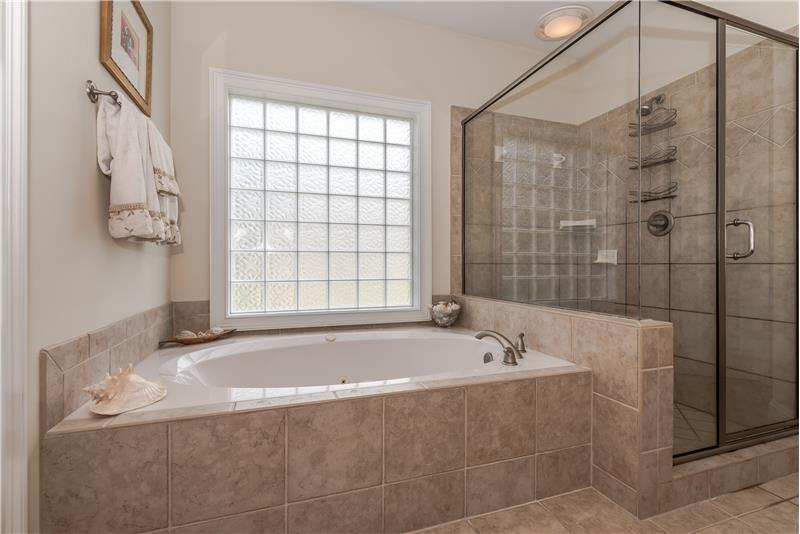 Spa-inspired master bath features deep, jetted soaking tub and large shower, both with tile surround.