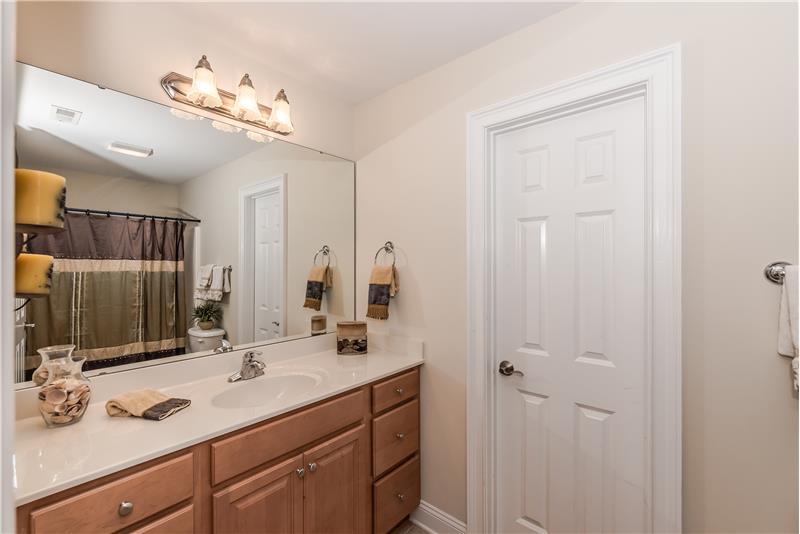 En-suite bathroom with extended vanity, tile floors, walk-in closet.