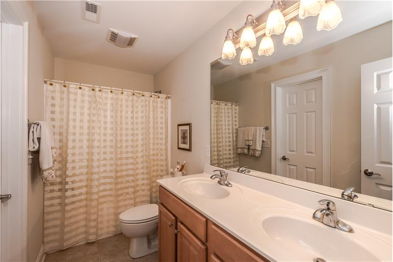 Shared bathroom on second floor of home with extended double sink vanity, tile floors.