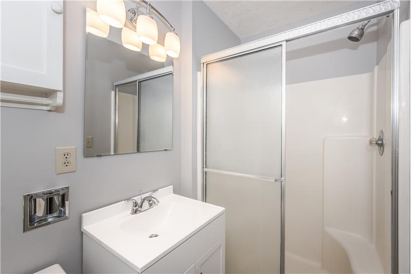 Updated master bathroom with step-in shower, tile floors, new light fixture