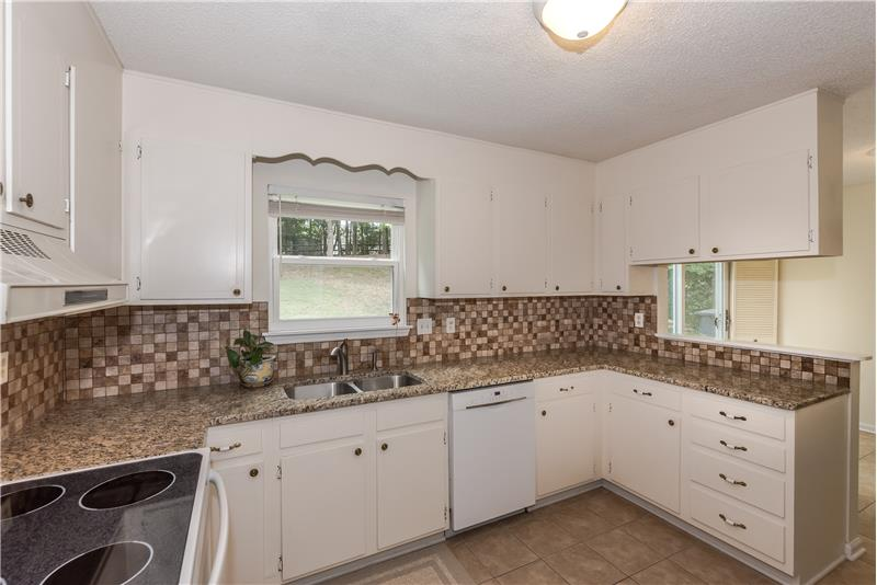Kitchen features granite counters, tile back-splash, tile floors