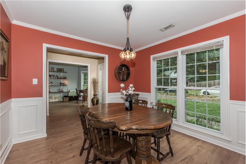 Dining room features mill work, French-style windows, designer light fixture.