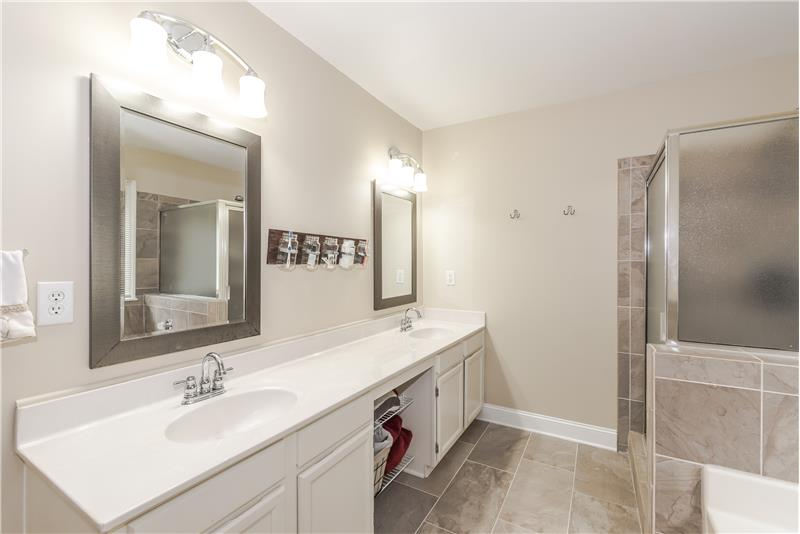 Master bathroom features tile, updated mirrors and lights, expansive dual sink vanity with storage below.