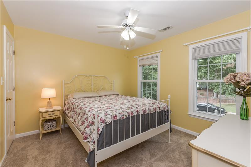 One of the home's secondary bedrooms with new carpet, ceiling fan/light.
