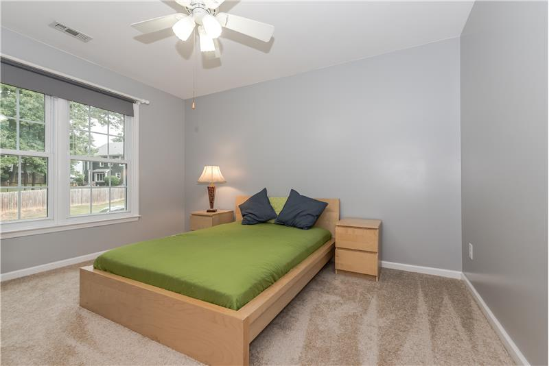 One of the home's secondary bedrooms with new carpet and ceiling fan/light.