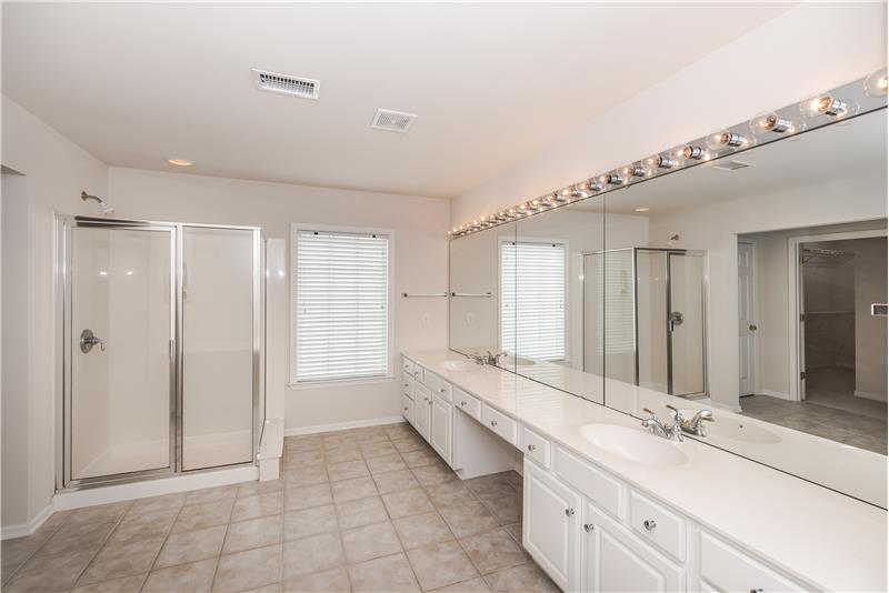 En-suite master bath features expansive, double sink vanity and step-in shower
