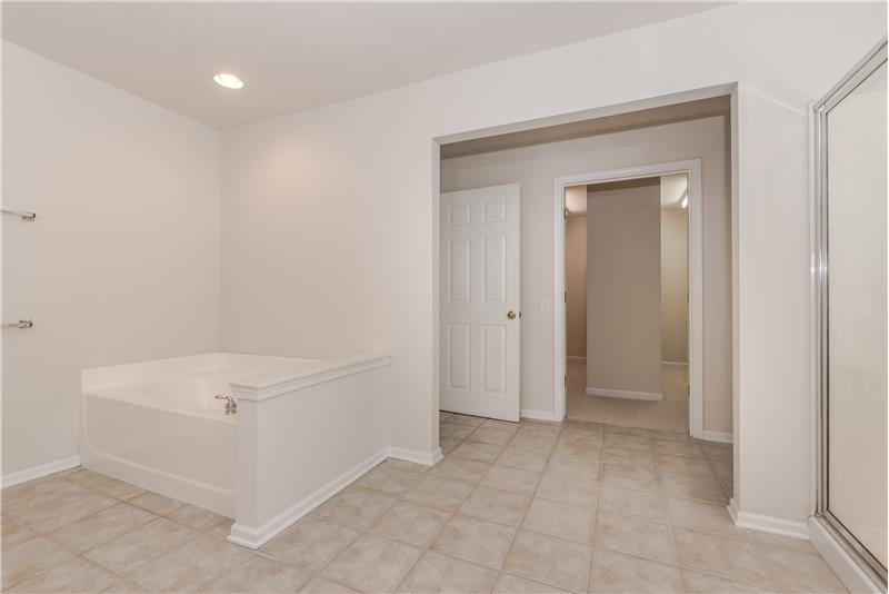 Soaking tub, private WC, linen closet, and tile floors round out the master bath picture