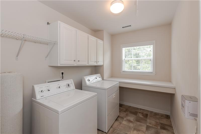 Large, windowed laundry room on second floor with folding table and cabinet storage.