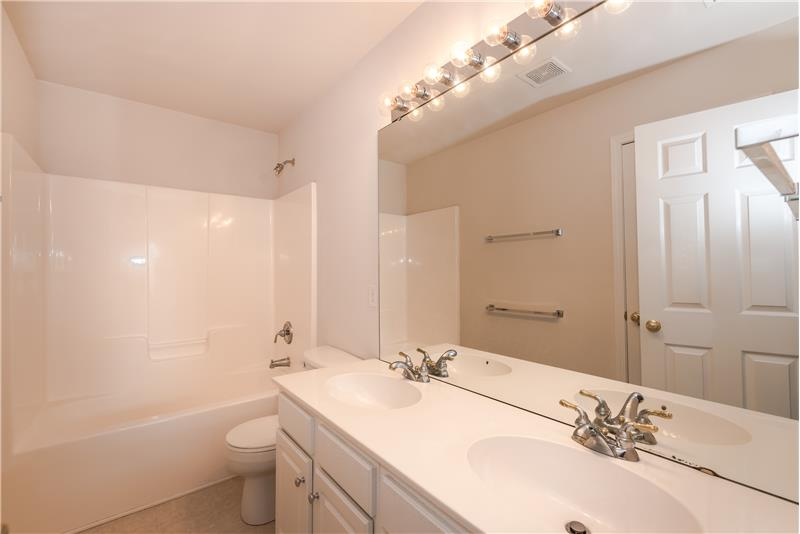 Hall bath shared by the three secondary bedrooms features double sink vanity, linen closet