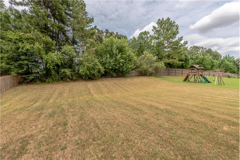 Flat, treed back yard perfect for play sets, kids, dogs...
