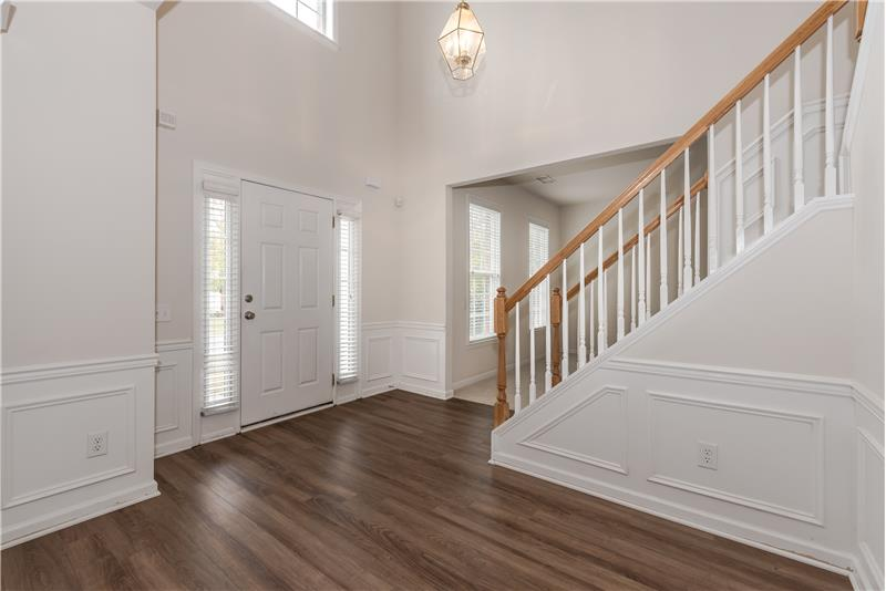 Bright, sunny 2-story foyer with brand new flooring provides a lovely introduction to the home