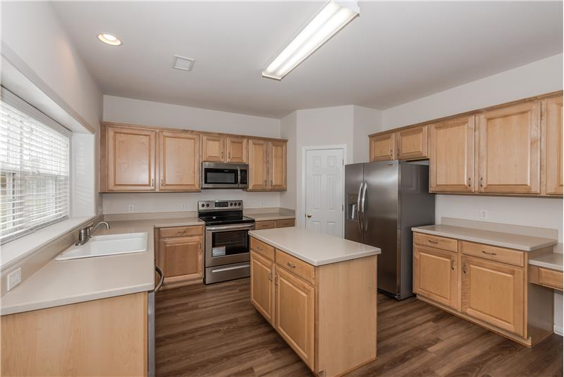 Kitchen with island, solid surface counters, planning desk, brand new stainless steel appliances